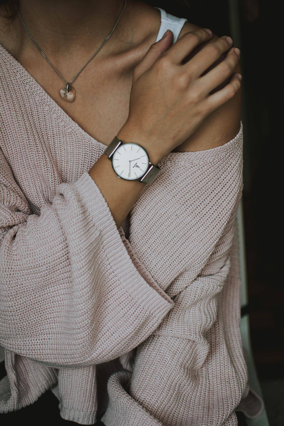 woman holds her shoulder while wearing a watch