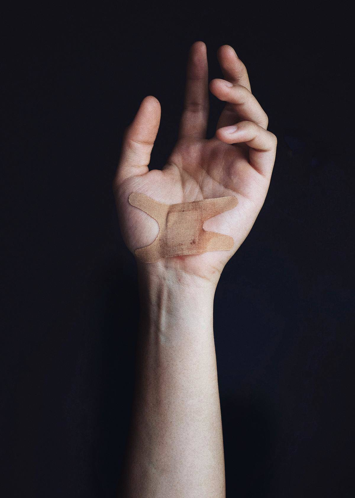 woman holds with bandaid on her hand