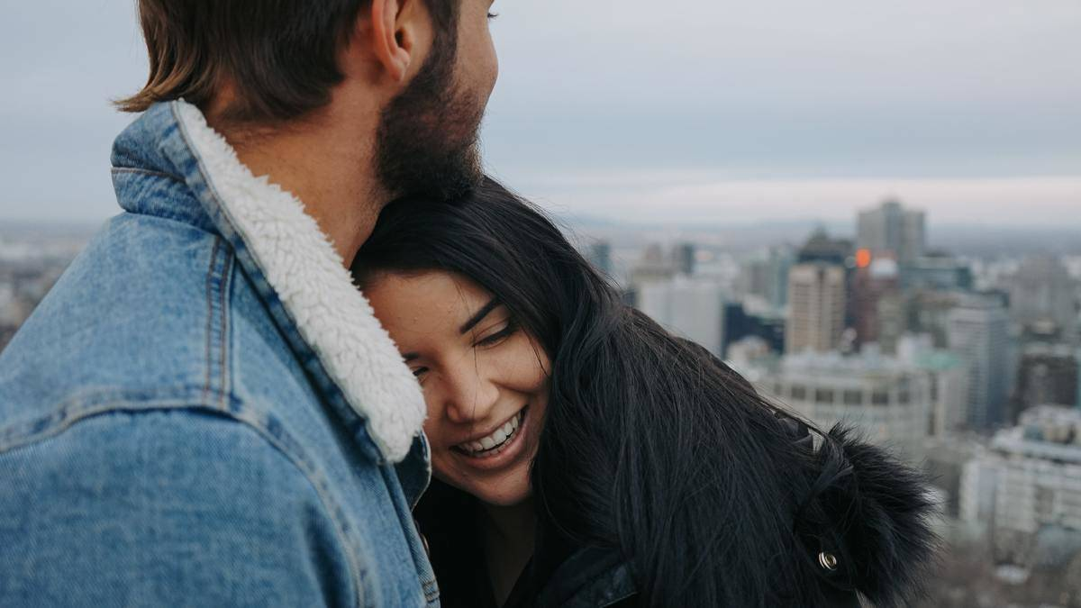 woman leaning head on man's chest smiling
