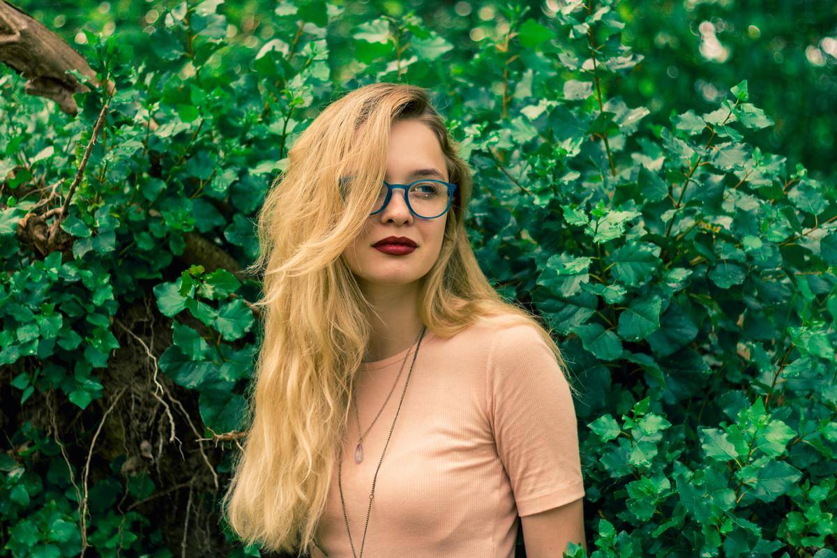 woman in peach shirt with long blonde hair looking serious in front of wall hedge