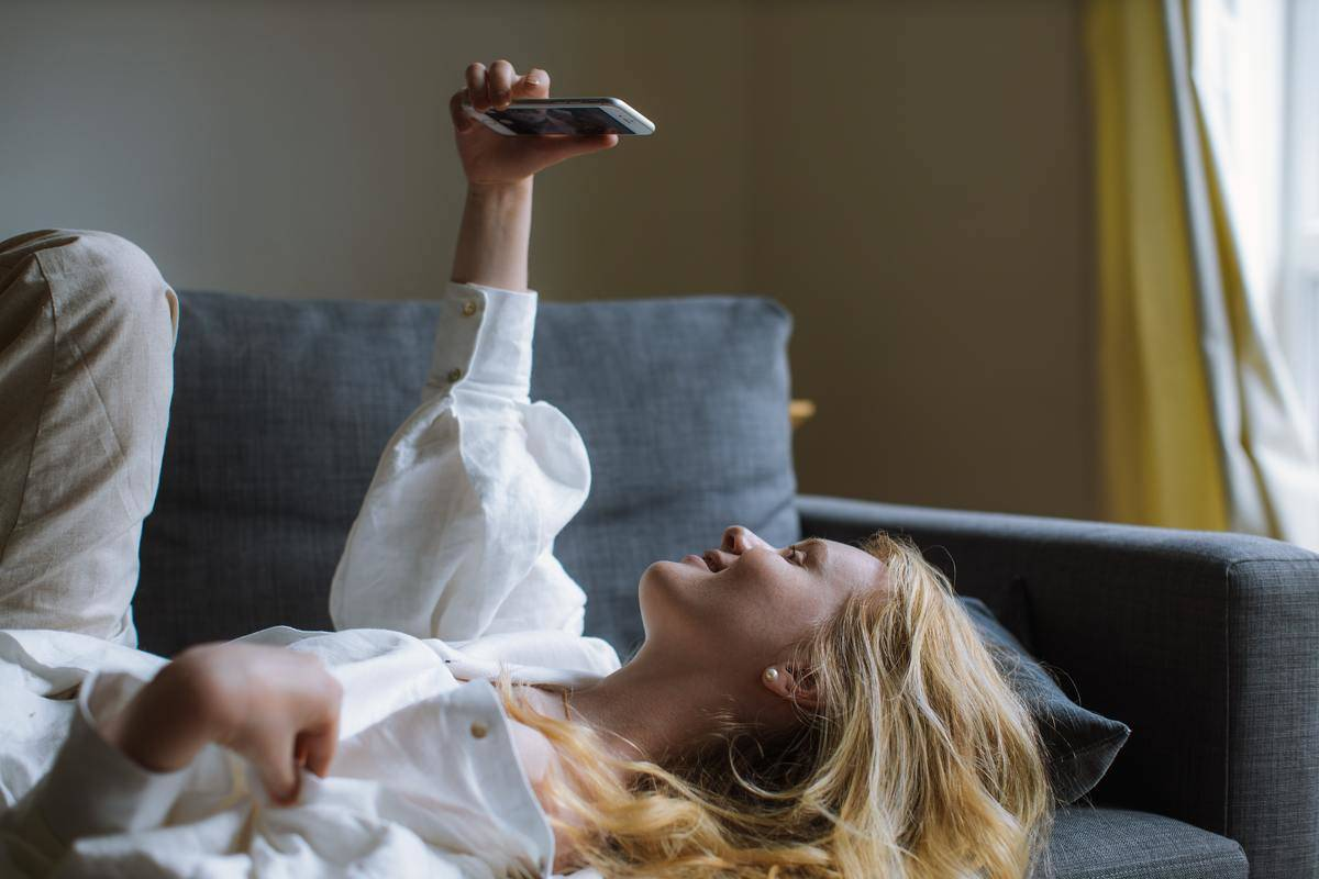 woman in white shirt lying on couch taking photo
