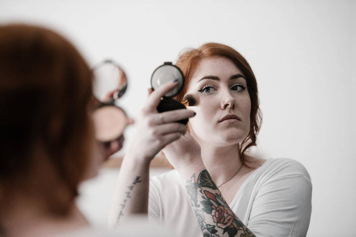woman in white tshirt with sleeve tattoos putting on makeup using compact mirror