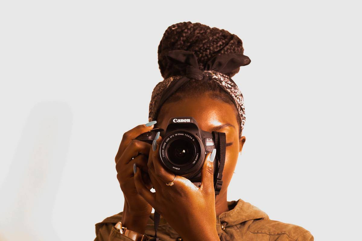 woman looking through professional canon camera lens