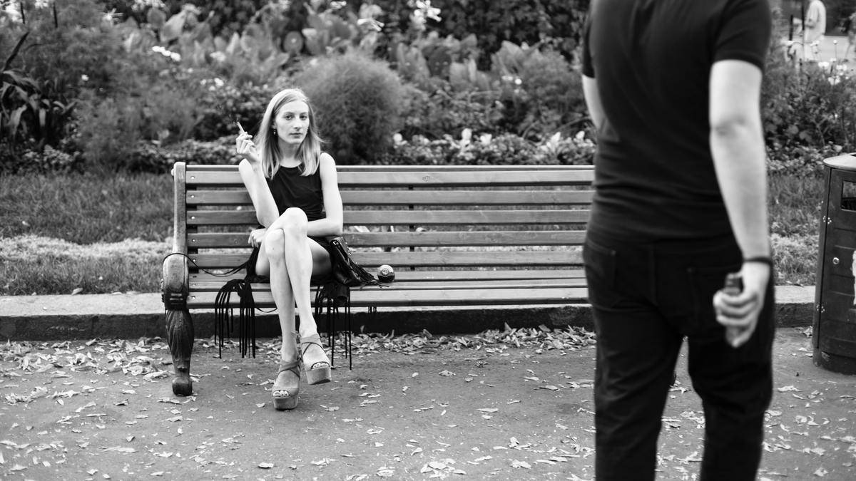 grayscale woman on bench seated looking judgmental at man walking past