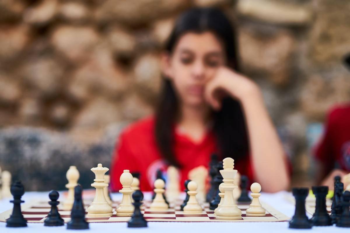 woman in background out of focus looking at chessboard in foreground