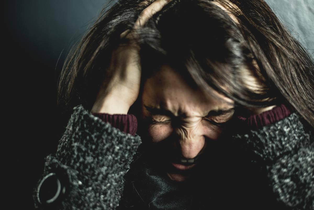 woman runs fingers through hair in anger