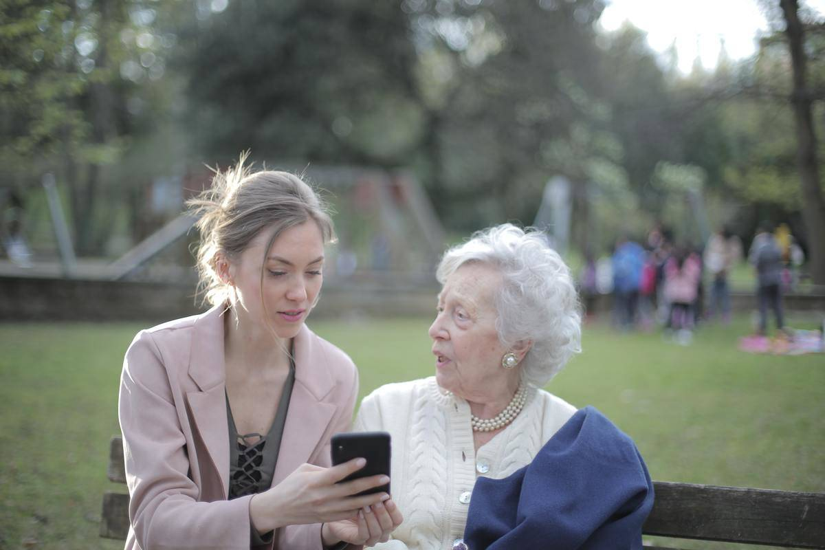 woman showing text to grandma in park