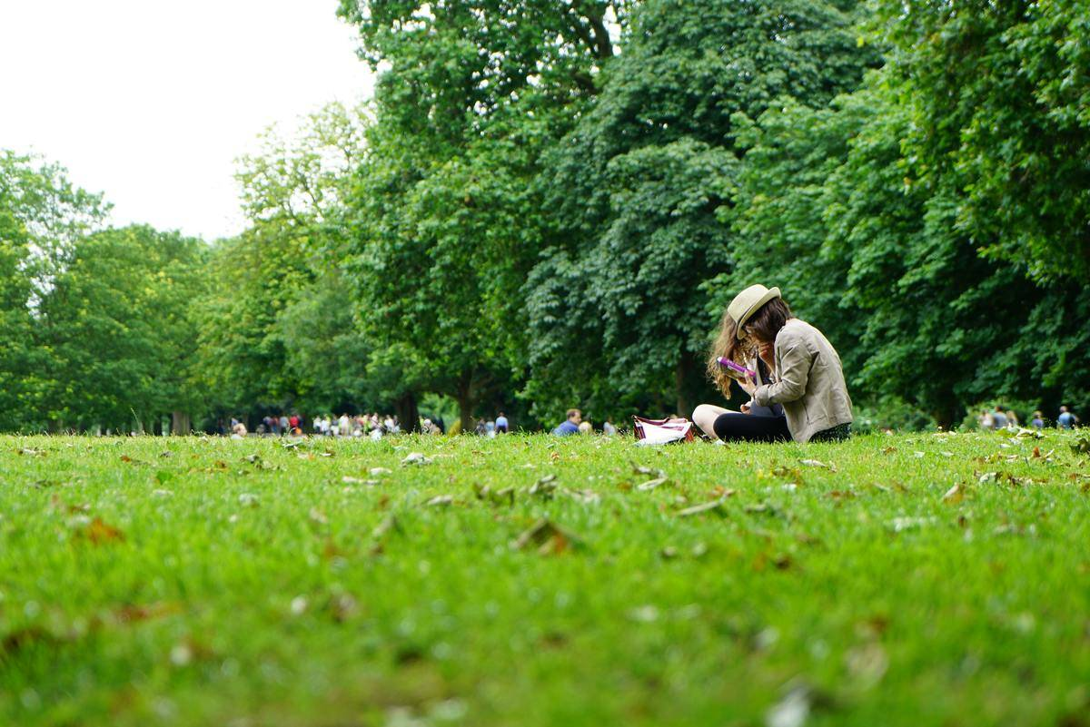 woman sits on grass in the park