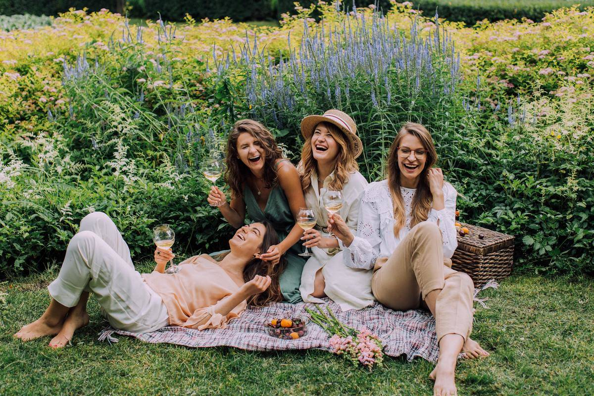 women sit for picnic and laugh