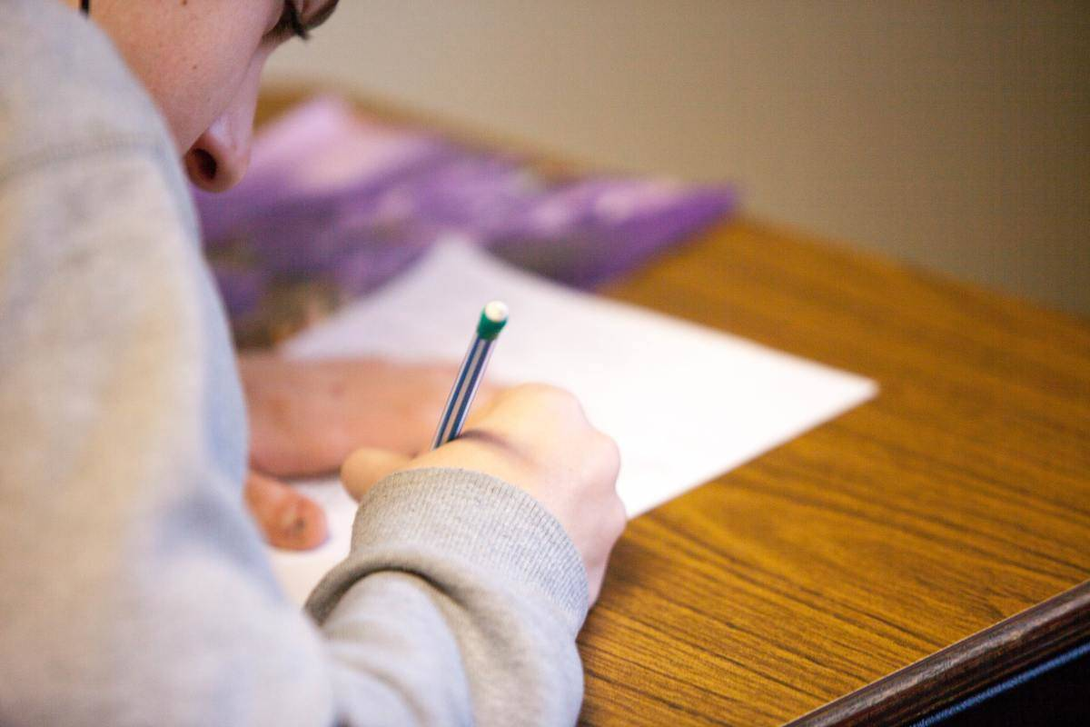 man writing focused on piece of paper