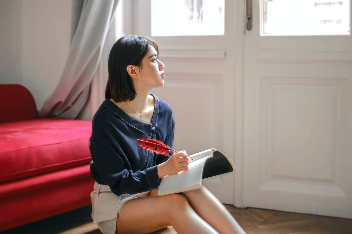 woman sitting alone indoors writing in a journal
