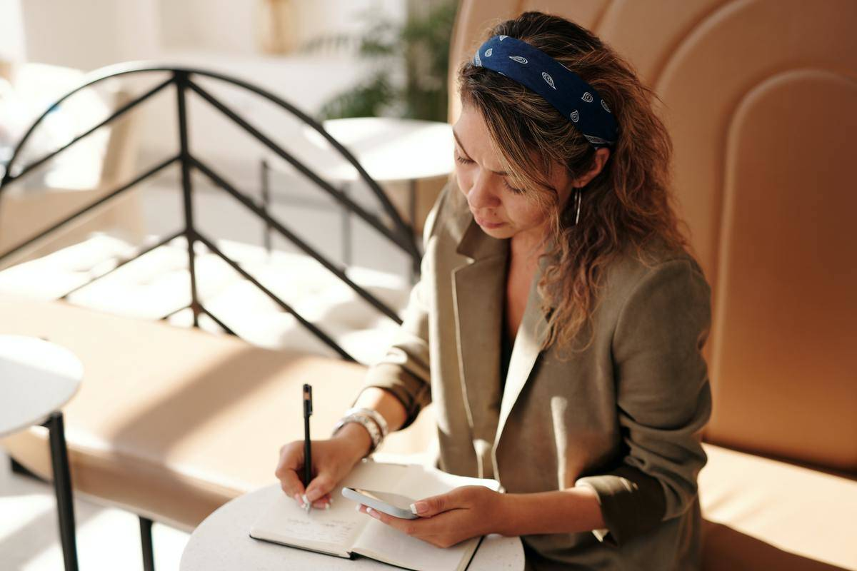 a woman looking at her phone and writing in a journal