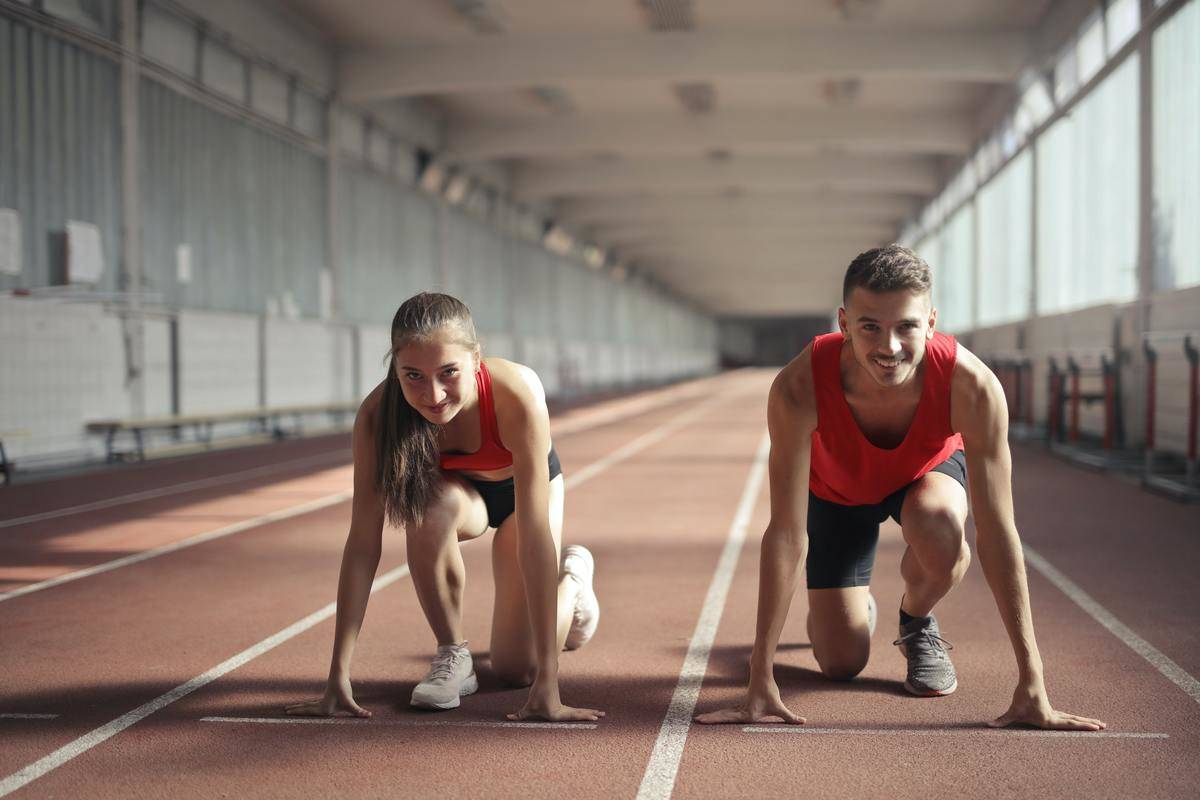 young man and woman in racing positions on track