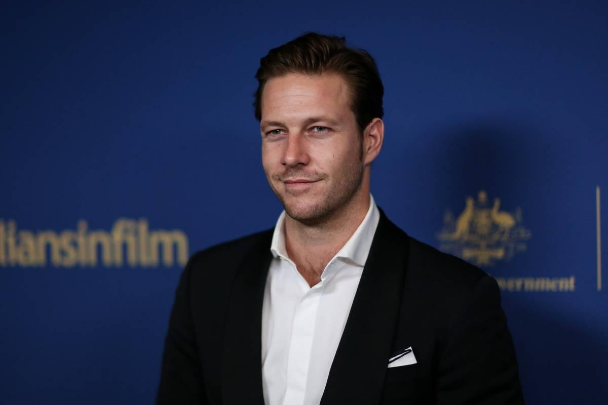 Actor Luke Bracey in a suit smiling at the camera attends the 2019 Australians In Film Awards in Los Angeles, California.