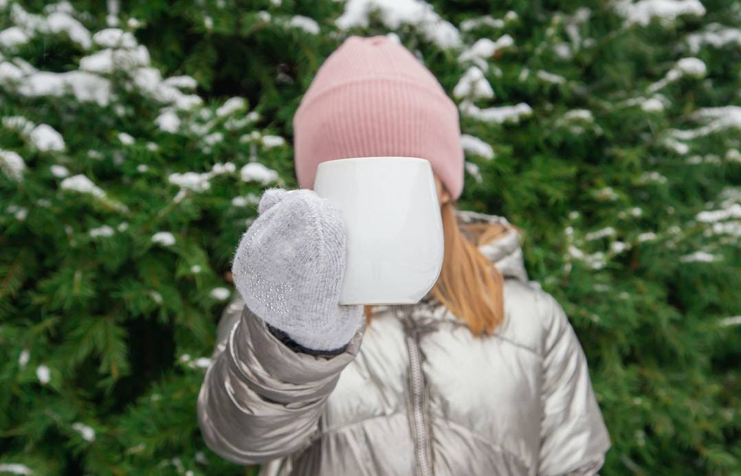 A beautiful blonde girl stands against the background of a green Christmas tree and covers her face with a white mug, which she holds in a winter, gray mitten.