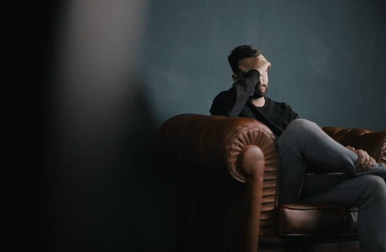 man sitting on leather couch with his head in his hand looking upset