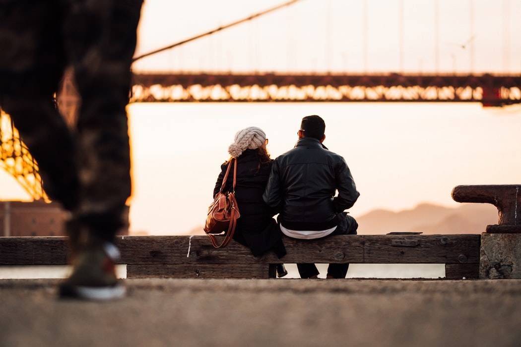 two people sitting together on a bench with a blurred background