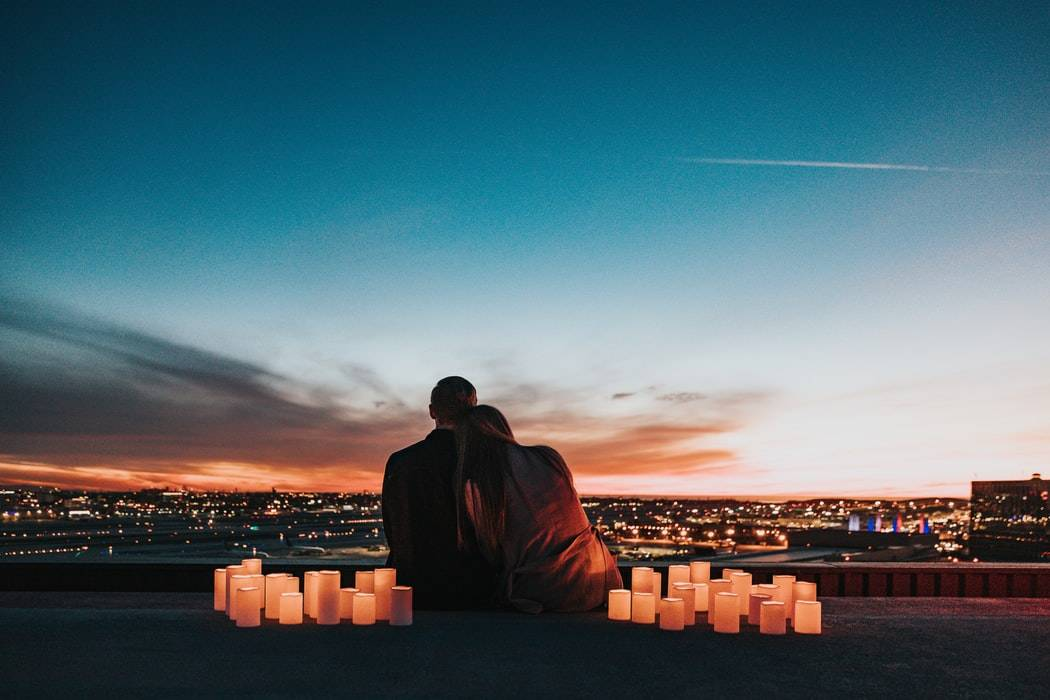 shot of couple's backs as they lean on each other and stare out at a city view with candles amongst them