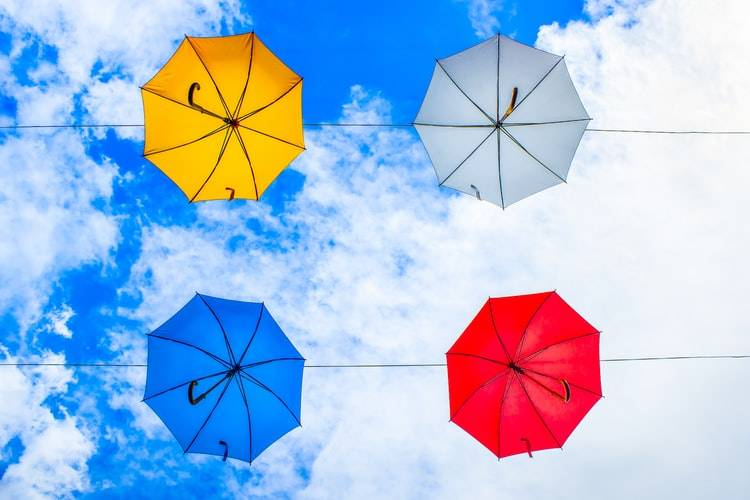 Four umbrellas floating in the sky in a square formation