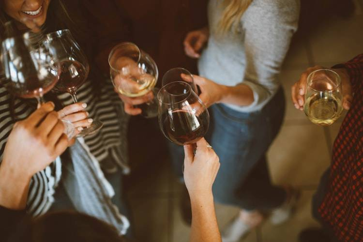 shot of lower bodies of a group of friends with wine glasses in their hands
