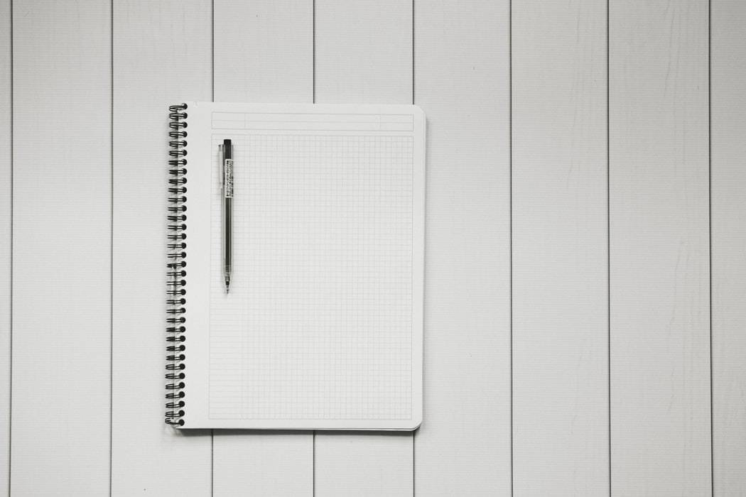 Grid notebook and Muji pen shot against a white background