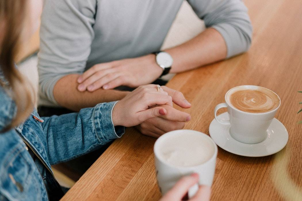 close up shot of two people holding hands with lattes in front of them