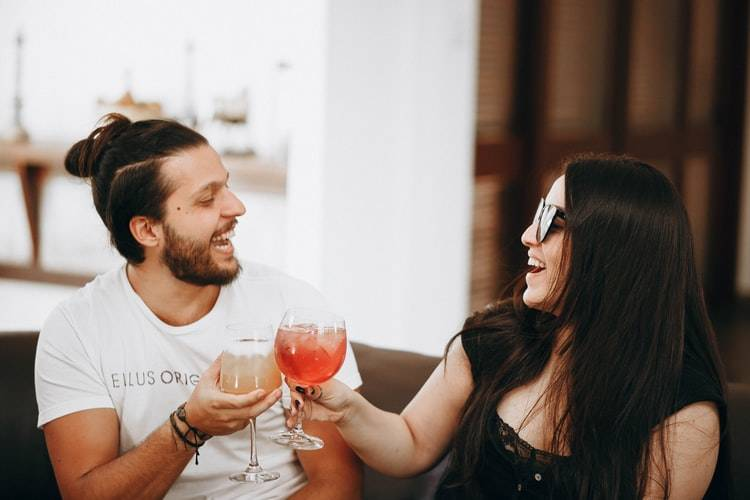 Man and woman laughing and celebrating with a toast