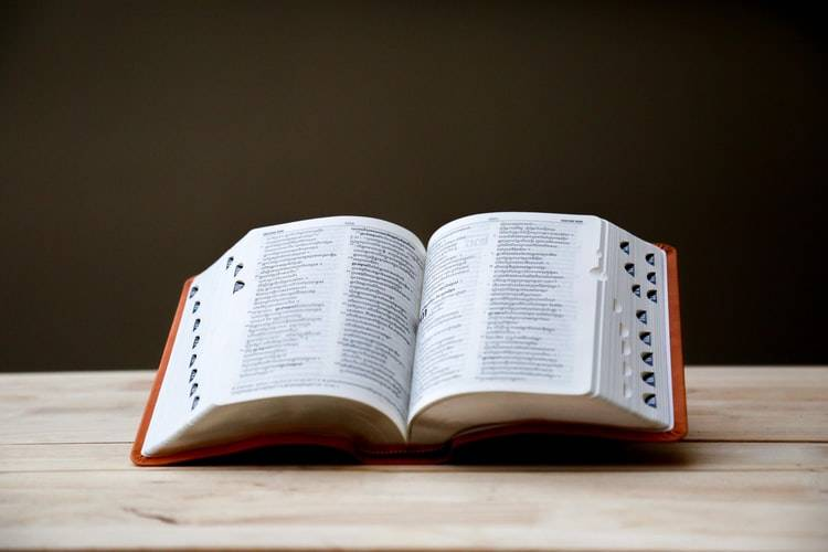 large open dictionary on a wooden table