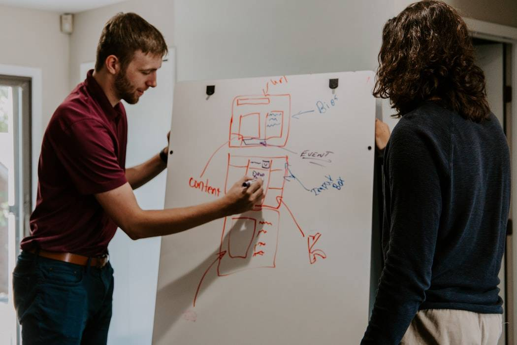 man and woman standing at whiteboard as the man writes something on it