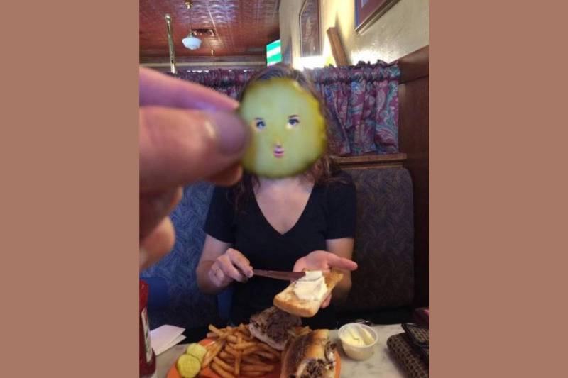Man holding up pickle slice over girlfriend's face to take a picture