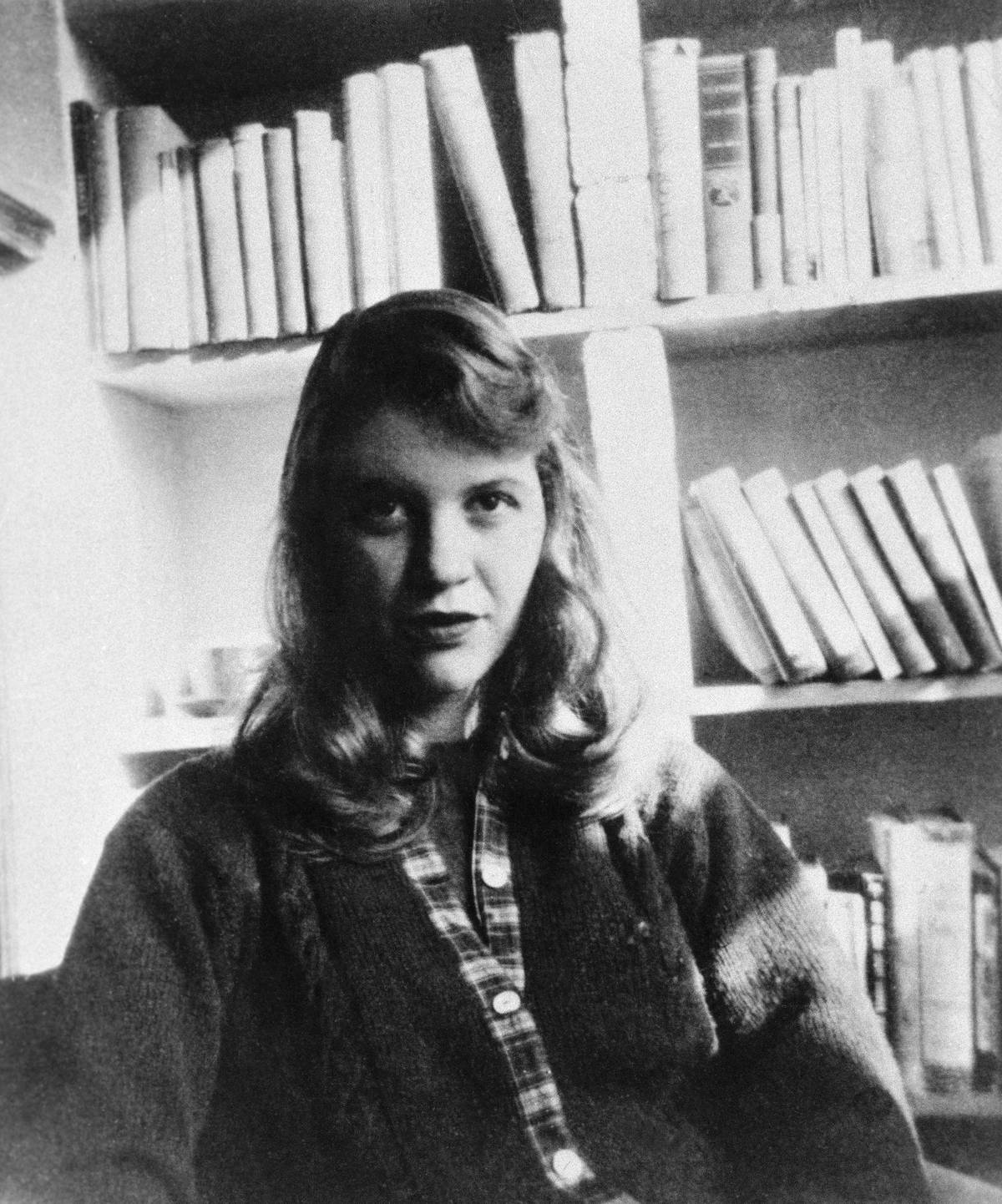 Photo shows author Sylvia Plath seated in front of a bookshelf.