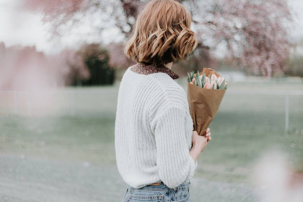 back shot of a woman holding a bouquet of spring flowers outside with a blurred background