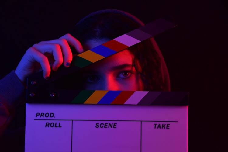 woman posing for a photo with a film clapperboard framing the upper half of her face