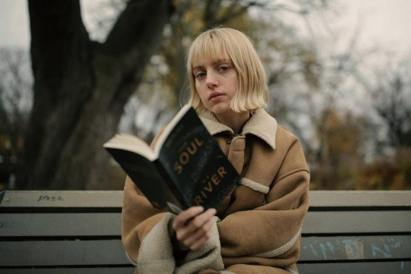 woman reading a book on a park bench as she looks up at the camera