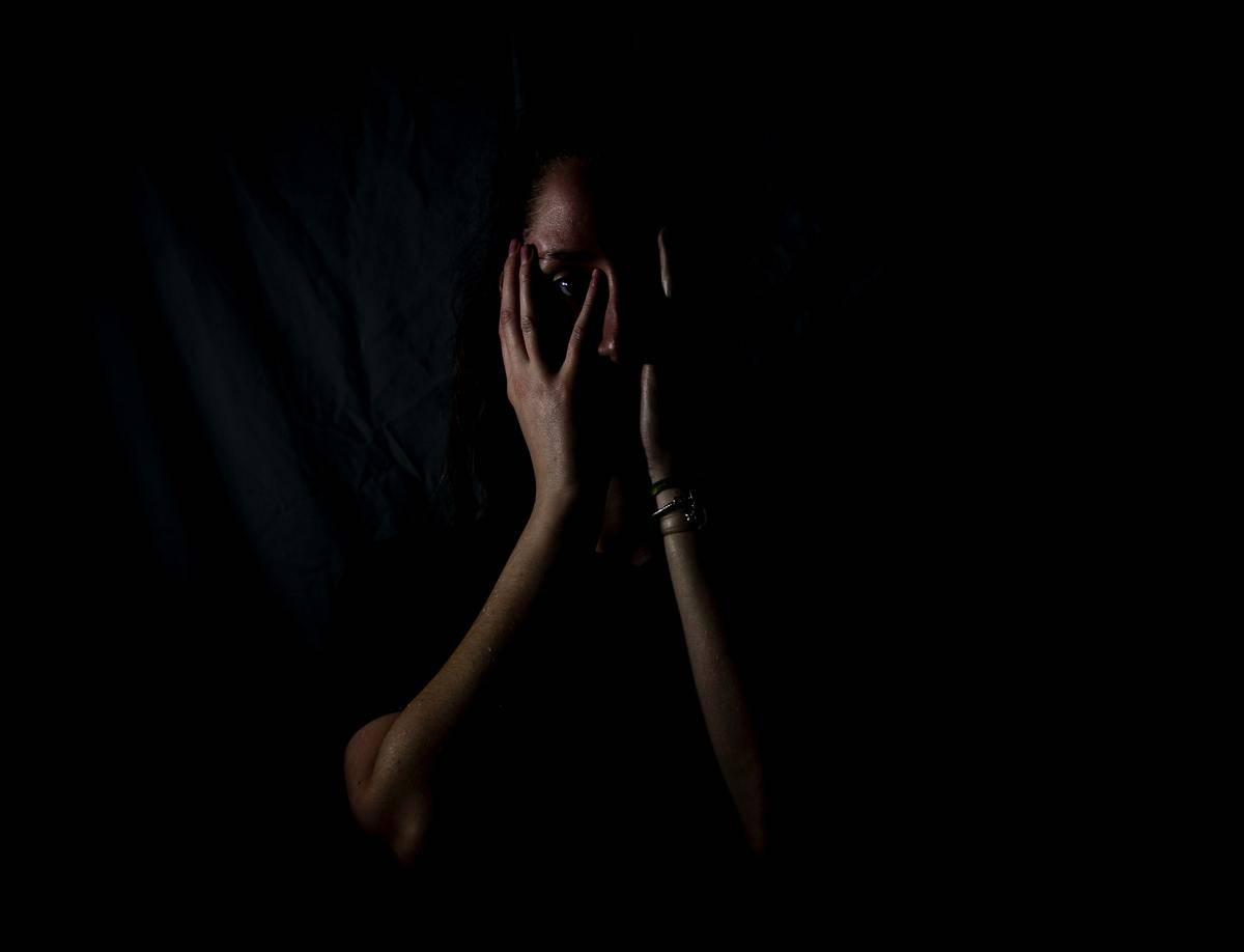 woman hiding her face in fear in black bakground