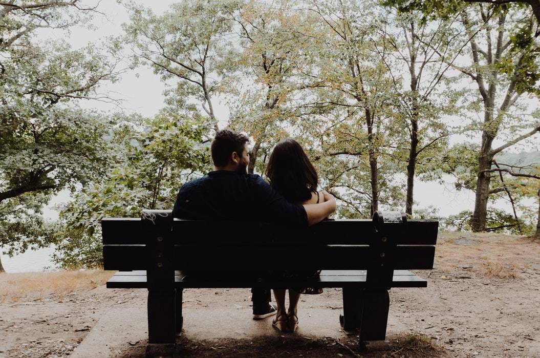 back shot of man and woman on park bench with arm around her