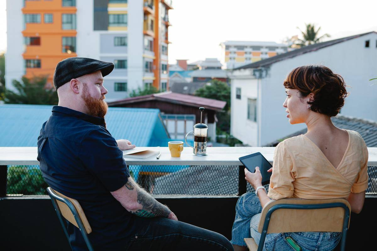 man and woman talking on balcony