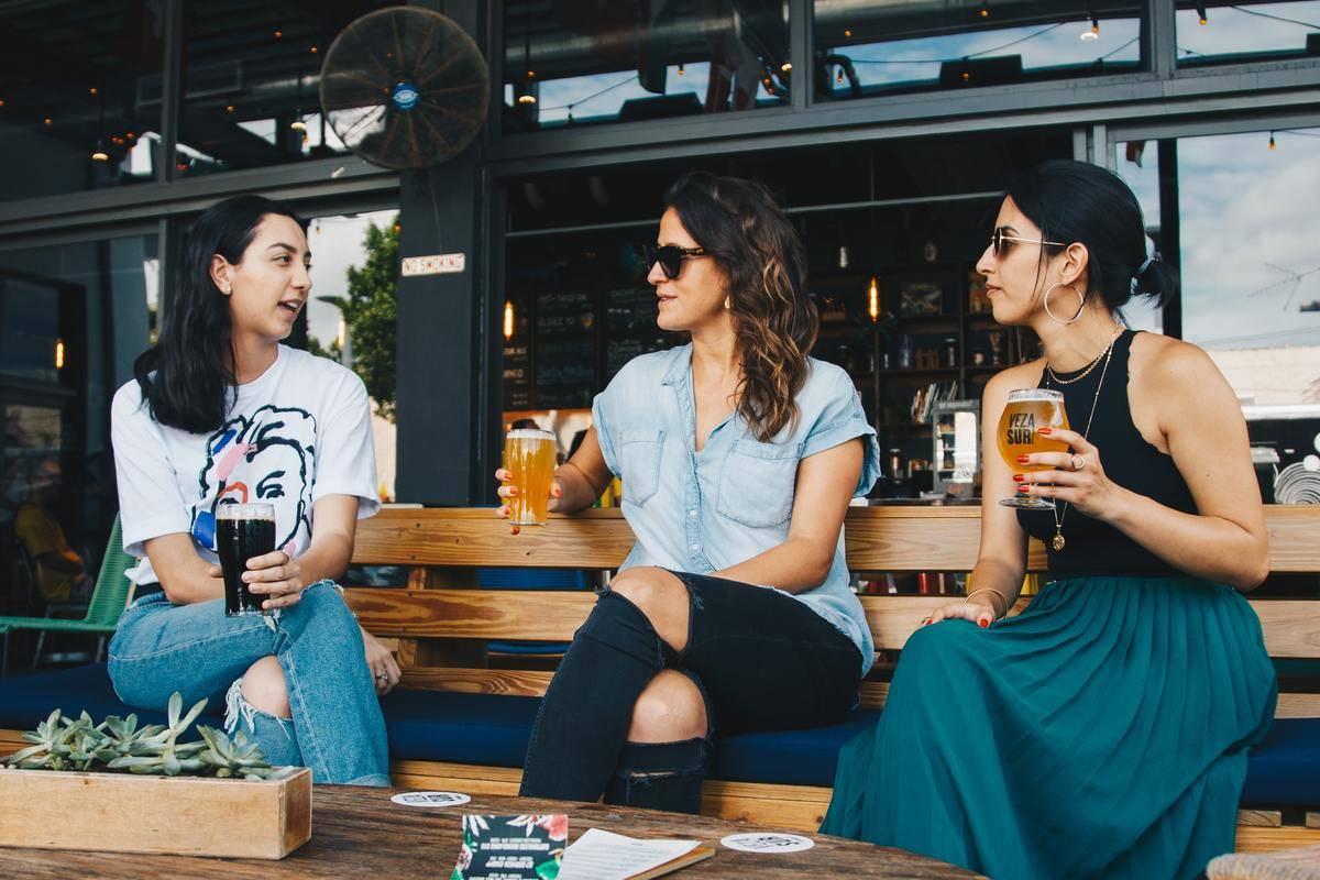 three friends sitting outside at a bar talking