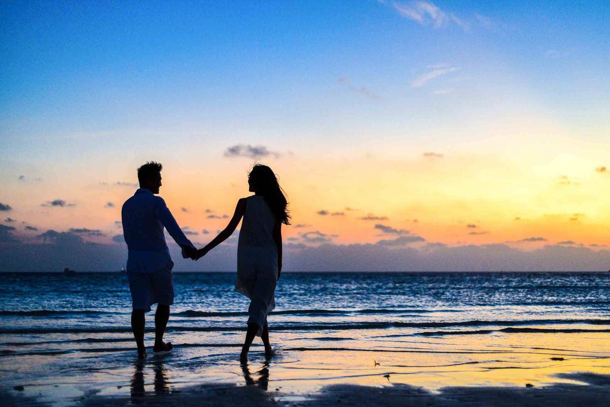 man and woman holding hands walking along the beach