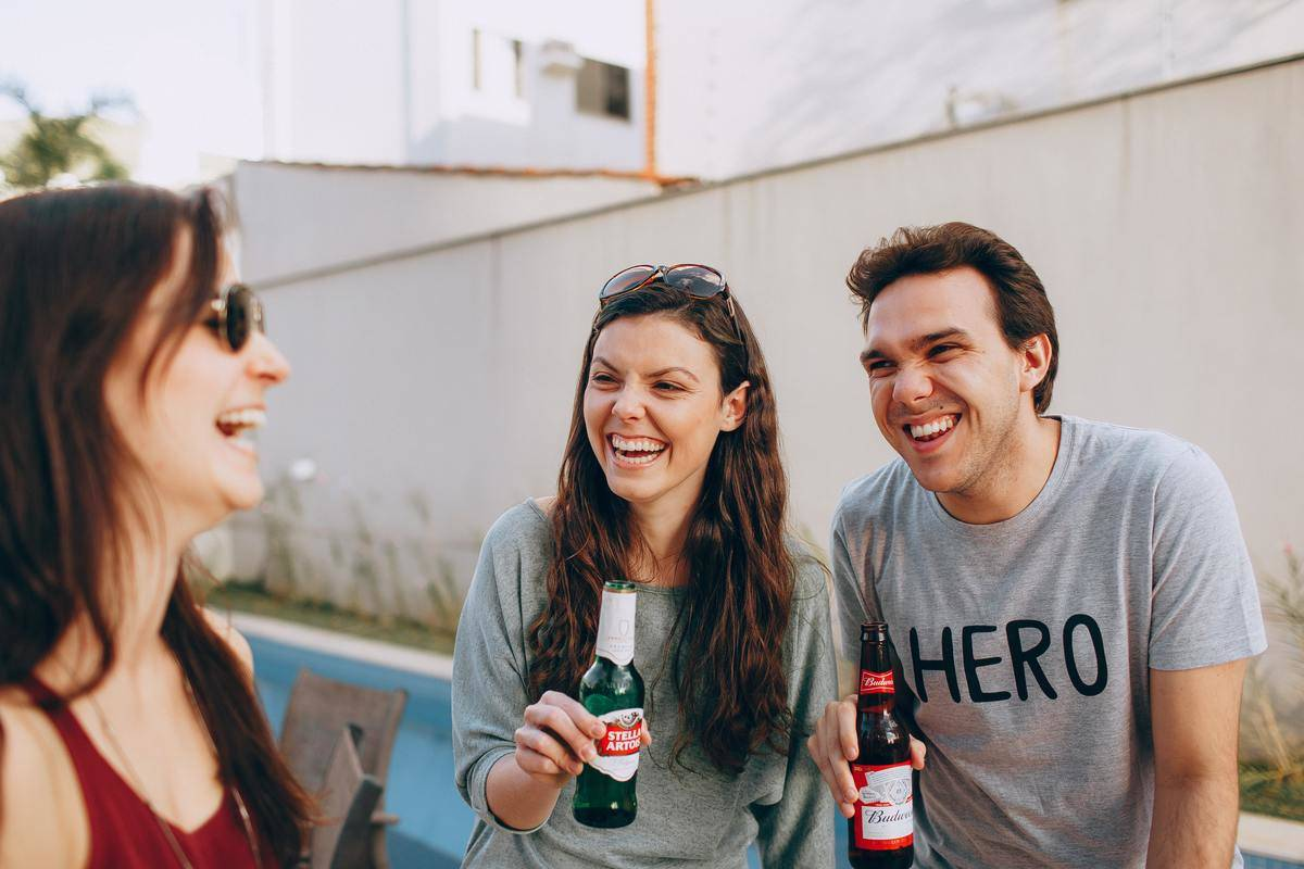 man and two women having a beer together