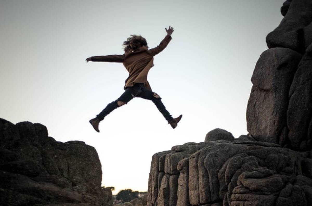 woman jumping across two cliffs