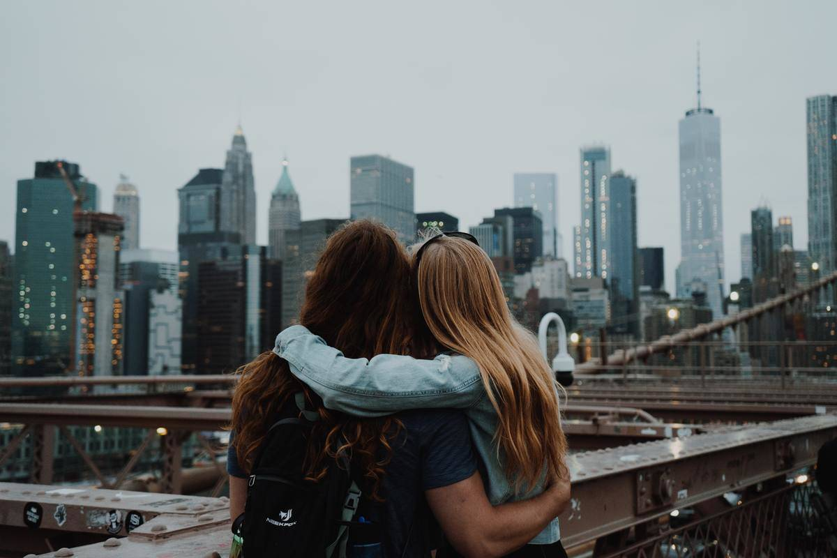 friends with an arm around each other looking out at the city view