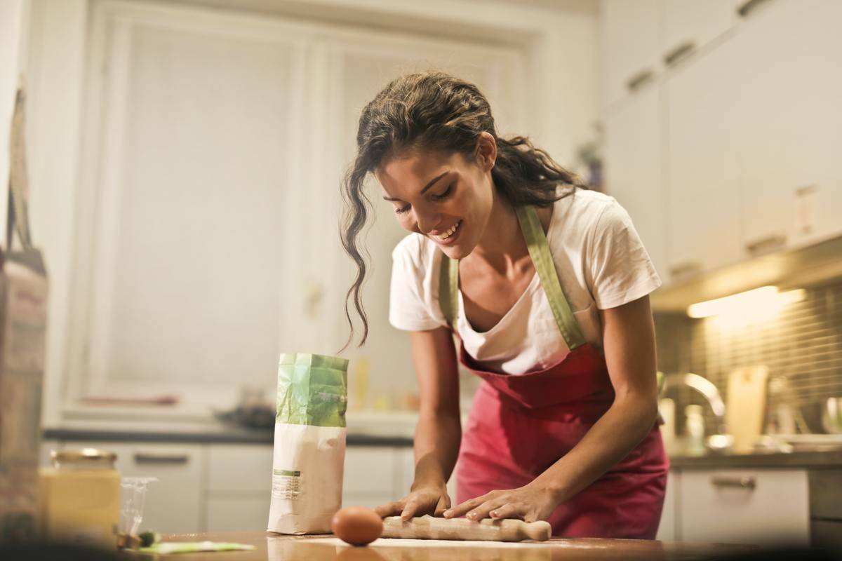 woman wearing apron cooking in kitchen