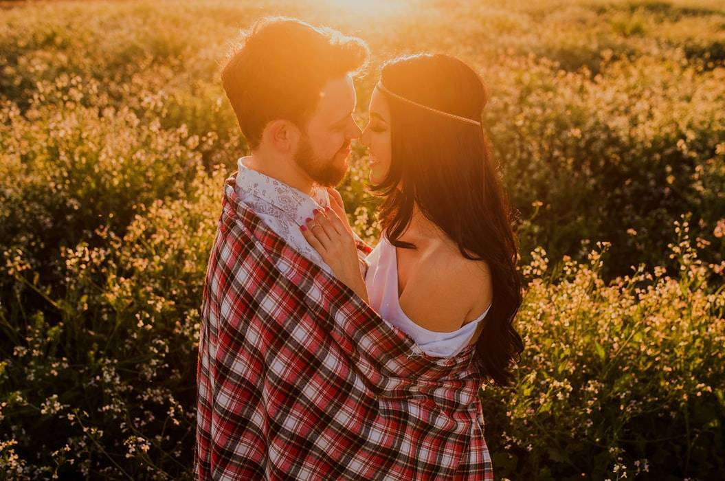couple about to kiss with man's flannel wrapped around the woman