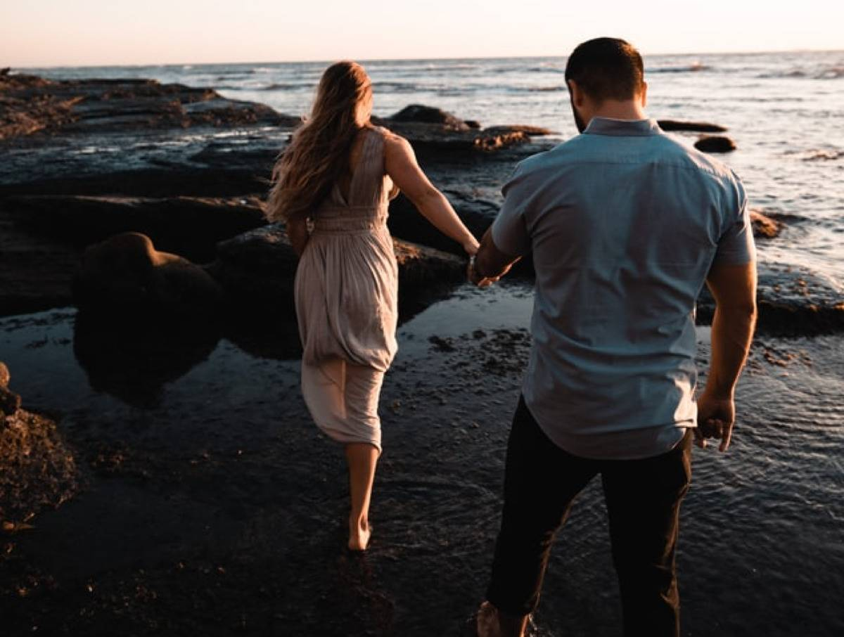 woman leading man holding hands on beach
