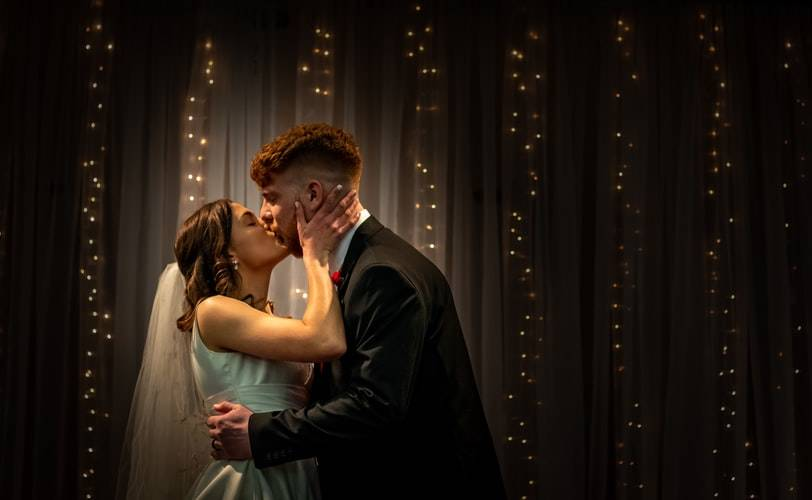 Dressed up couple passionately kissing against a pretty backdrop with fairy lights