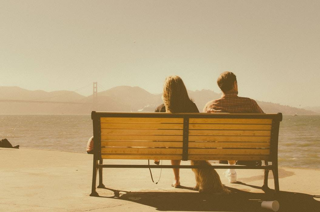 woman and man sitting on park bench with their dog