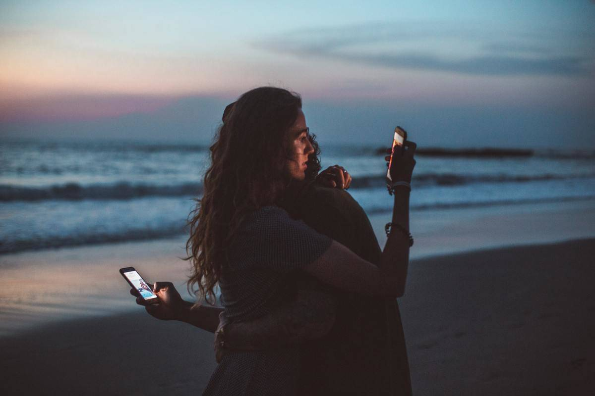 couple looking at their phones while hugging in the sunset