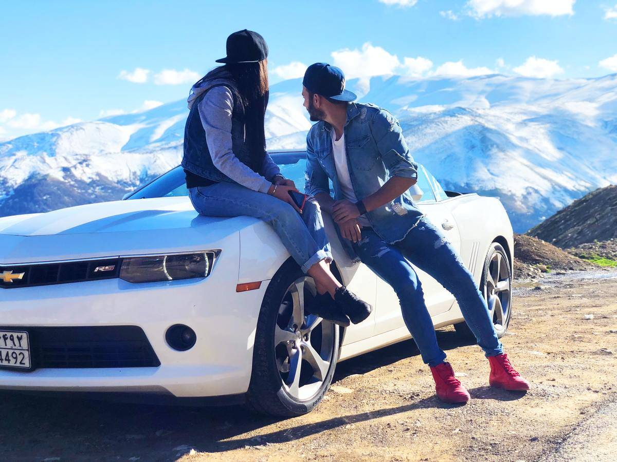 man and woman sitting on car look back at mountain