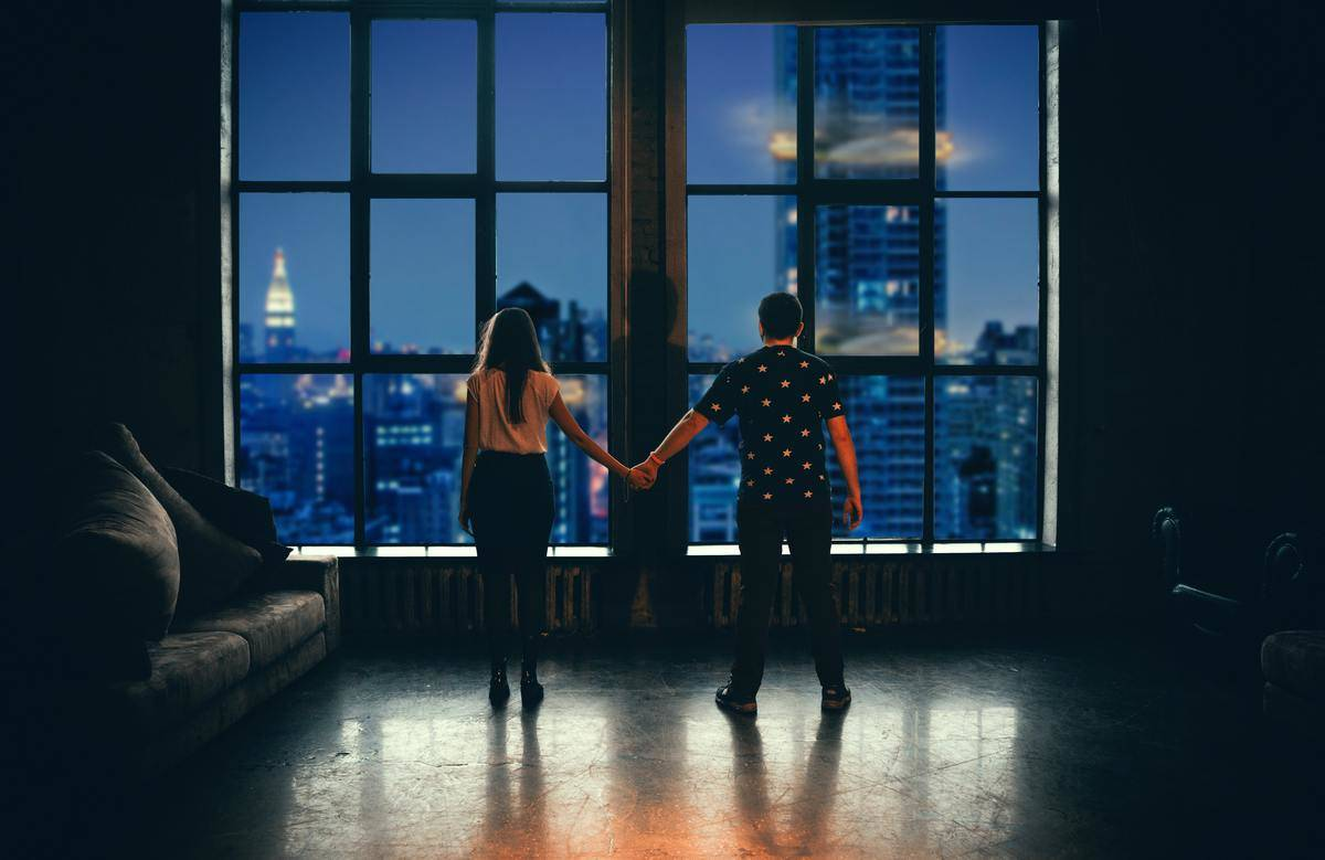 couple standing in front of big window holding hands